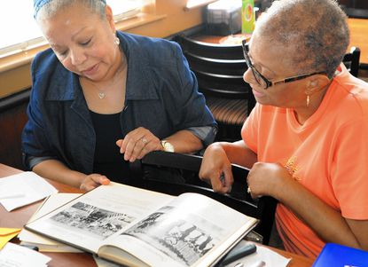 Former classmates Pamela Barner-Fant, left, and Sylvia Clark look through an old yearbook while planning their upcoming reunion. The last class to graduate from Central Consolidated High School in 1965 will have its 50th reunion Oct. 3
