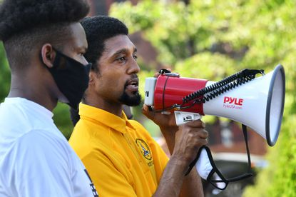 Baltimore City Council President Brandon Scott uses a megaphone June 3, 2020, ,to address a rally at War Memorial Plaza before protesters, led by a coalition of Baltimore youth movement groups, began a march downtown.