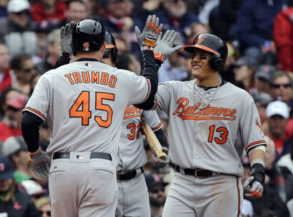 Baltimore Orioles' Mark Trumbo is congratulated at the plate from teammate Manny Machado (13) after his three-run homer against the Boston Red Sox in the third inning of a baseball game at Fenway Park, Monday, April 11, 2016, in Boston.