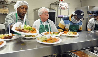 Volunteers serve a hot lunch at the Franciscan Center in Baltimore.