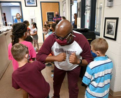 """Havre de Grace Elementary School Principal Ron Wooden, center, shares a few elbow bumps with students after they performed the song """" Thank You for Being a Friend"""" in the main office at the school for Wooden on the last day of school at Havre de Grace Elementary School Monday, June 14, 2021. Wooden has been at Havre de Grace Elementary School as principal for approximately seven years and will be leaving the school to be principal at William Paca-Old Post Road Elementary in the Fall."""
