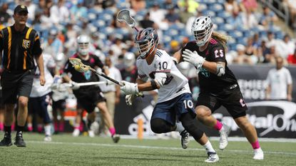 Archers' Stephen Kelly runs with the ball away from Chrome's Connor Farrell during a Premiere Lacrosse League game on Saturday in Foxborough, Mass. (Winslow Townson/AP Images for Premiere Lacrosse League)