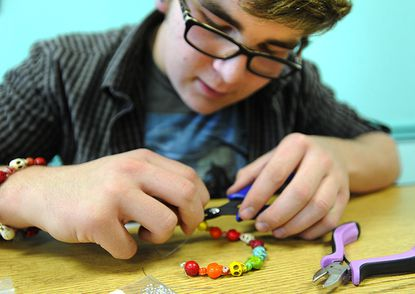 Volunteer Matthew Fuksa, 15, helps put the finishing touches on a skull-bead bracelet during a Dia de los Muertos program organized by members of the Teen Advisory Board at the Taneytown branch of the Carroll County Public Library Wednesday.