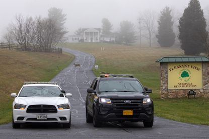 A deer crosses through the fog as a Carroll County Sheriff officer and a Maryland State Trooper guard the driveway to the Pleasant View Nursing Home, in Mount Airy, Md., Sunday, March 29, 2020. Pleasant View is one of the nursing facilities hard hit by the COVID-19 pandemic. (AP Photo/Jacquelyn Martin)