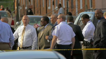 Investigators stand by at the command center a block away on Madison Street while Baltimore Police move forward at the 800 block Linwood during a scene of violence that culminated at an apparent barricade at the 800 block of Linwood Ave..
