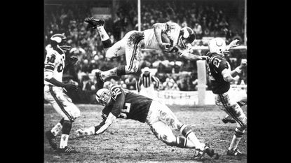 A Minnesota Viking player dives over Baltimore Colts linebacker Mike Curtis during game at Memorial Stadium on Sept. 19, 1971.