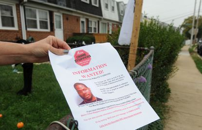 A neighbor holds a flier about Alonzo Gladden, who was shot and killed in the 2700 block of Marbourne Ave.