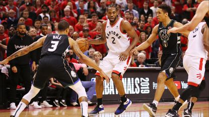 Raptors forward Kawhi Leonard watches for the double-team trap by Bucks guards George Hill and Malcolm Brogdon during Game 6.
