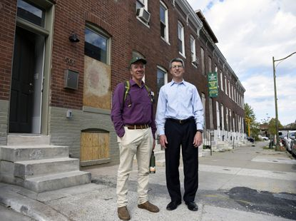 Ted Rouse and Ed Sabatino stand on North Milton Avenue, in front of a Station East house that is being completely rehabilitated. The train trestle can be seen at the end of the block.