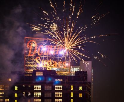Fireworks usher in the new Domino Sugars sign as it is lit over Baltimore's Inner Harbor on July 4th.