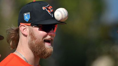 Orioles pitcher Andrew Cashner balances a ball on the brim of his cap at the Ed Smith Stadium complex in Sarasota, Fla.