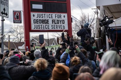"""People celebrate the guilty verdict in the trial of Derek Chauvin for the murder of George Floyd in Minneapolis on Tuesday April 20, 2021, as a sign is changed to show """"justice served."""" Derek Chauvin, a former Minneapolis police officer, was found guilty of second-degree unintentional murder, third-degree murder and second-degree manslaughter in the death of George Floyd while in police custody last year."""