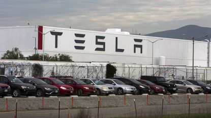 Cars are lined up near the Tesla Motors factory complex in Fremont, Calif.
