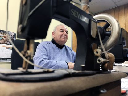 A toy sewing machine given by his wife frames Philip Spector, creator and CEO of Fashions Unlimited at 1100 Wicomico Street, which he has been designing and modifying.