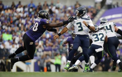 Ravens outside linebacker Elvis Dumervil grabs onto Seattle Seahawks quarterback Russell Wilson after Wilson threw a pass during an NFL football game, Sunday, Dec. 13, 2015, in Baltimore.