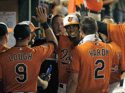 Orioles teammates congratulate Jimmy Paredes after he hit his first home run as an Oriole, a solo shot, to put the club ahead.