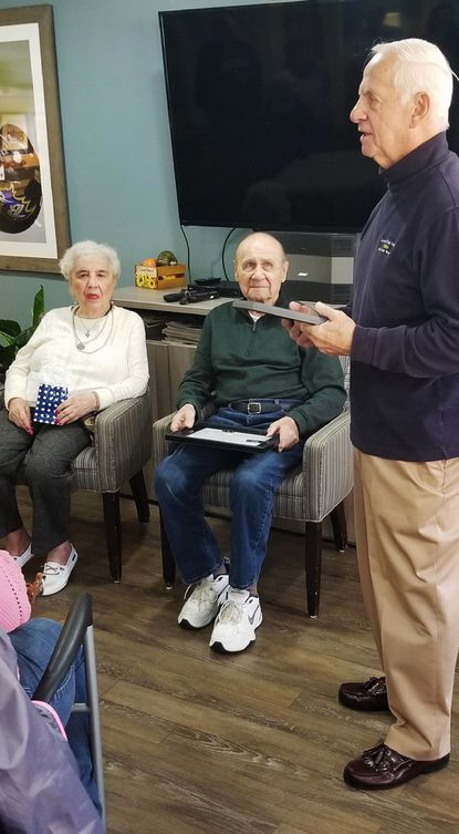 """Frank Lupashunksi, center, with his wife Anna Lupashunski, receives a plaque of thanks from Larry Corum for service in the U.S. Navy during World War II and teaching at Howard High from its opening day in 1952 until 1984. Former students of """"Mr. Lupe"""" gathered to honor him at Lighthouse Assisted Living in Ellicott City."""
