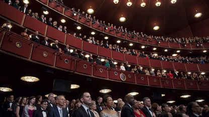 US President Barack Obama and First Lady Michelle Obama stand alongside the Kennedy Center Honorees for the national anthem as they attend the 2013 Kennedy Center Honors award ceremony at the Kennedy Center in Washington on December 8, 2013.