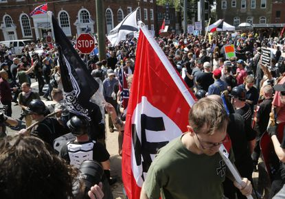 A white supremacist carries a Nazi flag into the entrance to Emancipation Park in Charlottesville, Va. in the summer of 2017. How many such men may now be trying to sabotage Black Lives Matter protests? (AP Photo/Steve Helber)