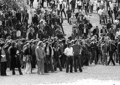 """<p>Around 3,000 people gathered for an anti-war rally on the Commons of Kent State University on May 4, 1970. Ohio National Guardsman, who had been called to the campus after protesters and local police had a violent confrontation the week before, fired at the protesters, killing four and injuring another nine people. The shootings triggered student strikes nationwide and """"began the slide into Watergate, eventually destroying the Nixon administration,"""" according to Jerry M. Lewis and Thomas R. Hensley of Kent State University.</p> <p>[Pictured: View of students at an anti-war demonstration at Kent State University in Ohio on May 4, 1970.]</p> <p></p>"""