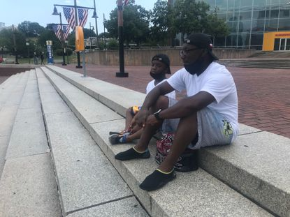 Billy Wright (right) and son Cameron Wright feed birds at the Inner Harbor Saturday. The father and son were drawn to the harbor because of the uncharacteristic lack of crowds on the holiday.