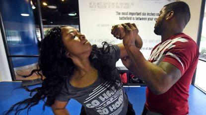 Christina Ellis, left, and Tawan Ramseur, both of Baltimore, take turns practicing self-defense moves during a Krav Maga self-defense class in Columbia. Krav Maga is practical self-defense training developed by Israeli special forces.