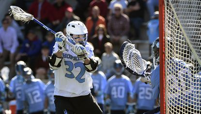 Johns Hopkins' Shack Stanwick, left, shoots and scores on North Carolina goalie Brian Balkam for Hopkins' sixth goal of the game in the third quarter on Feb. 28, 2016.