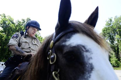 Tom Thelan, a member of the Howard County Volunteer Mounted Patrol program, sits atop his horse, Max, in Savage Mill Park.