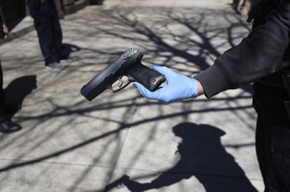 A Baltimore City Police Department central district officer holds a Ruger P94 pistol in the 1100 block of St. Paul Street April 5 after a man was taken into custody.