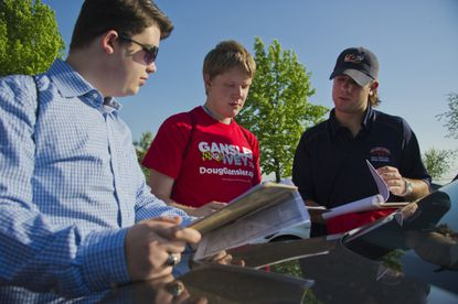 From left, Brady Widener, Tyler Beckey, and Patrick Battista, volunteers for the gubernatorial campaign of Doug Gansler check their information before they break out to canvass the area in a late push for the Democratic candidate.