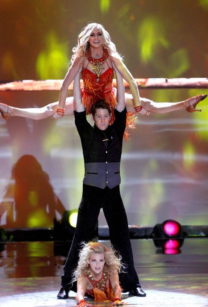 """Top 20 contestants Lindsay Arnold, Nick Bloxsom-Carter and Witney Carson perform a Latin Ballroom routine to """"Dance Again,"""" choreographed by Jason Gilkison."""