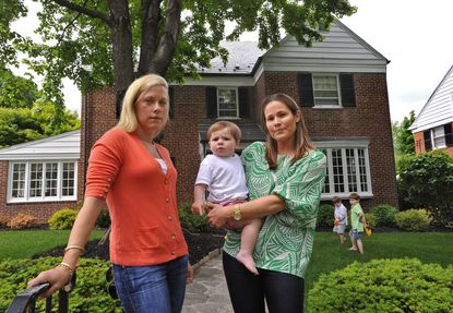 Katie Pinheiro, left, a resident of Croydon Road in Homeland, received a water bill recently for almost $500. Ridgely Bowman, right, holding son Drew, who lives in the house at right, said her family had received a bill for almost $600. Both families usually have water bills in the low $100s.