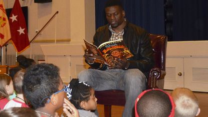 """Ravens tight end Benjamin Watson reads students """"The Remarkable Farkle McBride,"""" written by John Lithgow, at Aberdeen Proving Ground."""