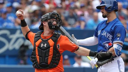 Chance Sisco #15 of the Baltimore Orioles throws out Kevin Pillar #11 of the Toronto Blue Jays who is thrown out attempting to steal second base in the second inning during MLB game action at Rogers Centre on June 9, 2018 in Toronto, Canada