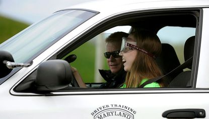 Liberty High School senior Allie Stallings wears goggles that simulate alcohol impairment as she drives with Cpl. Christopher Daly, of the West Chester, Pa. Police Department, during a class on the dangers of impaired driving at the Maryland Police and Correctional Training Commissions Driver Training Facility in Sykesville Wednesday.