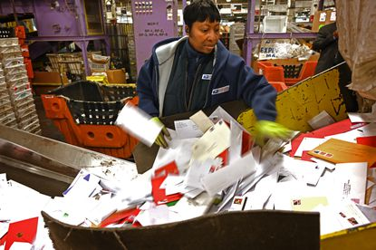 In this December 2019 file photo, postal employee Tru Wright separated packages from letters at Baltimore's Main Post Office.