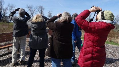 Family members of the late Chandler Robbins, famed ornithologist for whom a SkyWatch at the Howard County Conservancy is named, spot a Red-Shouldered Hawk during a dedication ceremony at the Conservancy.
