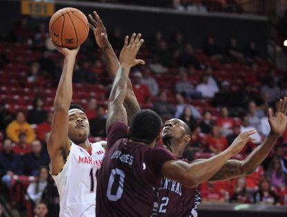 The Terps' Jared Nickens, left, shoots over North Carolina Central's Dante Holmes, center, and Jordan Parks in the second half at Xfinity Center.