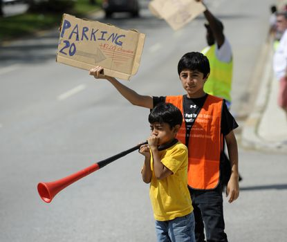Edward Ortega, 8, blows a vuvuzela while his brother Alexander, 13, holds a parking sign on Northern Parkway prior to the Preakness.