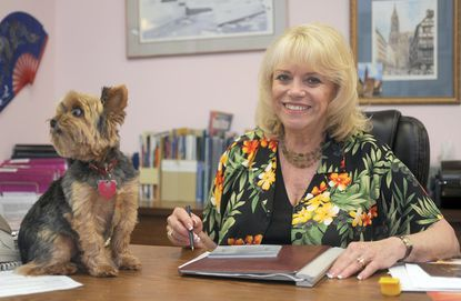 "Travel agent Lynda Maxwell is the owner of Destinations Travel. She is shown working in her office, accompanied by her Yorkshire Terrier Duke, the office's ""official greeter."""