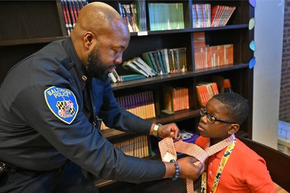 Officer Charles Lee, a volunteer mentor, instructs Booker T. Washington Middle School sixth grader Bryant Carraway, 12, on the art of tying a necktie at a mentoring activity organized by Corey Witherspoon.