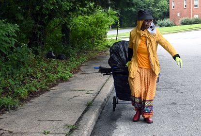 """Earlene Brown, 81, wheels several bags of trash up S. Wickham Road after sweeping debris from the 4800 block of Stafford Street. Brown, who says """"I got tired of sitting down,"""" recently moved to the area and adds, """"This is what I did when I was on the East Side."""" July 25, 2020. (Kim Hairston/Baltimore Sun)."""