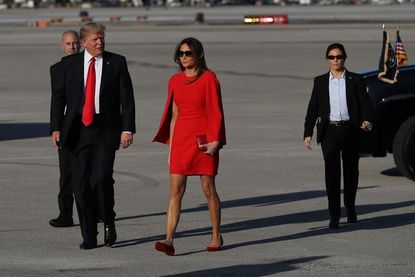 President Donald Trump walks with his wife Melania Trump on the tarmac after he arrived on Air Force One at the Palm Beach International Airporton Friday, Feb. 3, 2017.