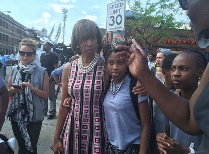 State Sen. Catherine Pugh (center) puts her arm around a young girl on Tuesday afternoon near intersection of Pennsylvania and West North avenues. A police commander at the scene said officers tried to arrest an armed man when his weapon fell and went off.