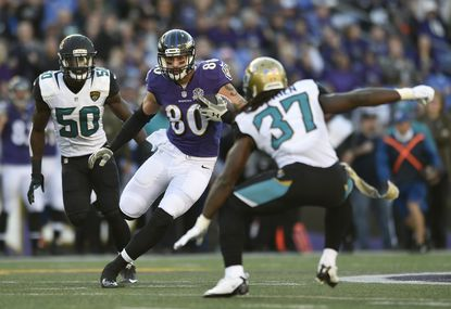 Ravens tight end Crockett Gillmore (80) rushes the ball around Jacksonville Jaguars outside linebacker Telvin Smith, back left, and strong safety Johnathan Cyprien in the first half, Sunday, Nov. 15, 2015, in Baltimore.