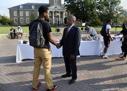 A student is greeted by David Wilson, right, President of Morgan State University, on his first day as a freshman industrial engineering major in this 2015 photo. (Barbara Haddock Taylor/Baltimore Sun)