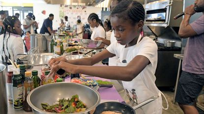 Chelsie Manning, 10, of Edmondson Village takes part in The Black Girls Cook Kids Food and Wellness Festival cooking competition.