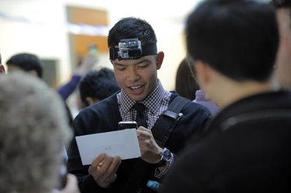 John Pang, Baltimore, uses a video camera strapped to his forehead to capture the moments he will want to remember on match day. He is holding his envelope moments before he and his Johns Hopkins University School of Medicine class find out where they will do their residencies. He matched the University of California at San Diego.