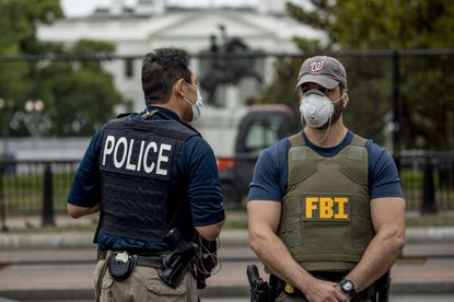The White House is visible behind a large security fence as uniformed Secret Service and FBI agents stand on the street in front of Lafayette Park in the morning hours in Washington, D.C. on Tuesday, as protests continue over the death of George Floyd. About 120 members of the Maryland National Guard will be sent to Washington, according to a Guard spokeswoman. (AP Photo/Andrew Harnik)