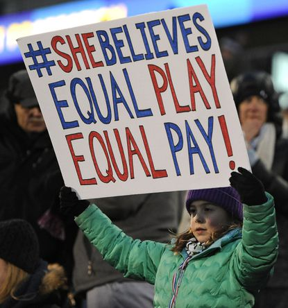 In this April 6, 2016, file photo, a girl holds up a sign for equal pay for the U.S. women soccer players, during the first half of an international friendly soccer match between the United States and Colombia, in East Hartford, Conn.